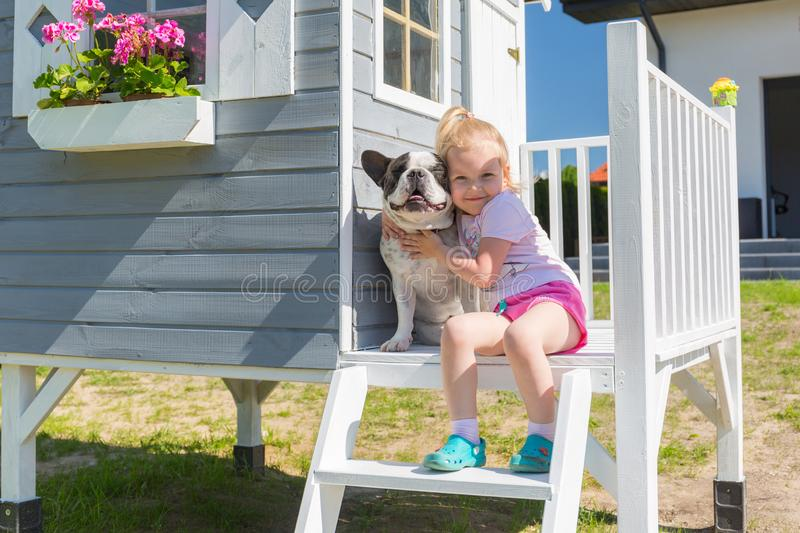 Little girl portrait with the dog at the beautiful garden house royalty free stock image