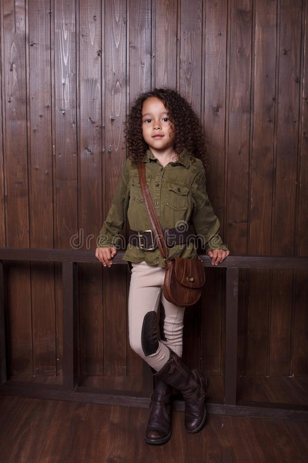 Little girl posing against the background of a wooden wall stock photos