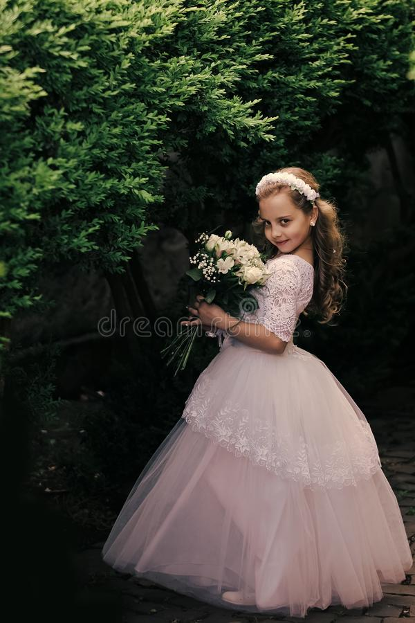 Little girl is posing in evening dress. Bride girl, bridesmaid and wedding ceremony. stock photos