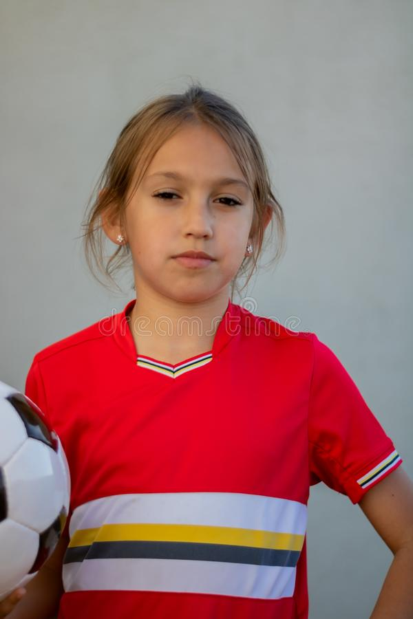 Little girl posing. With football player luggage child game back light kid childhood rear exercise red one sporty youth outside young soccer league uniform stock photography