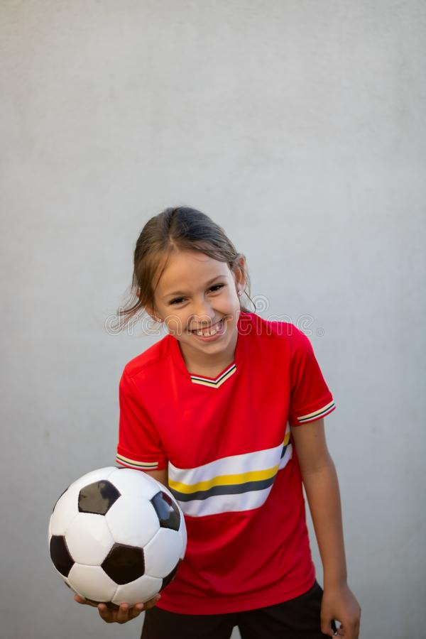 Little girl posing. With football player luggage child game back light kid childhood rear exercise red one sporty youth outside young soccer league uniform stock image