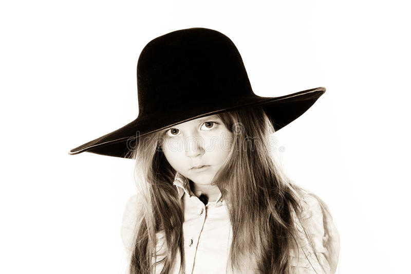 LIttle girl posing like a model in mother`s hat. Isolated on white background royalty free stock photos