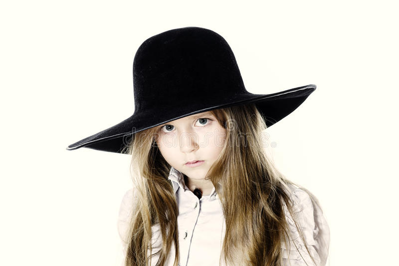 LIttle girl posing like a model in mother`s hat. Isolated on white background royalty free stock image