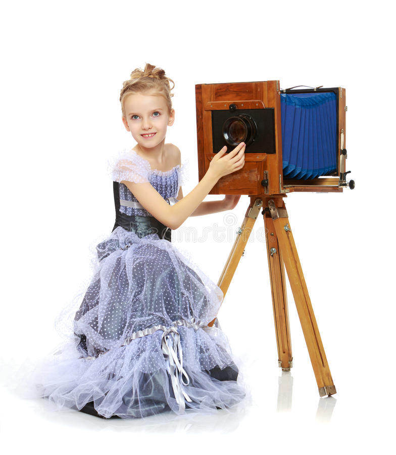 Little girl posing near the old camera. stock images