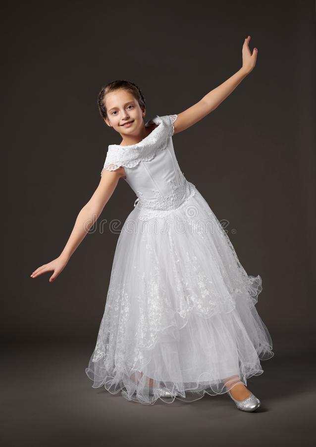 Little girl is posing in a white ball gown, dark background royalty free stock photo