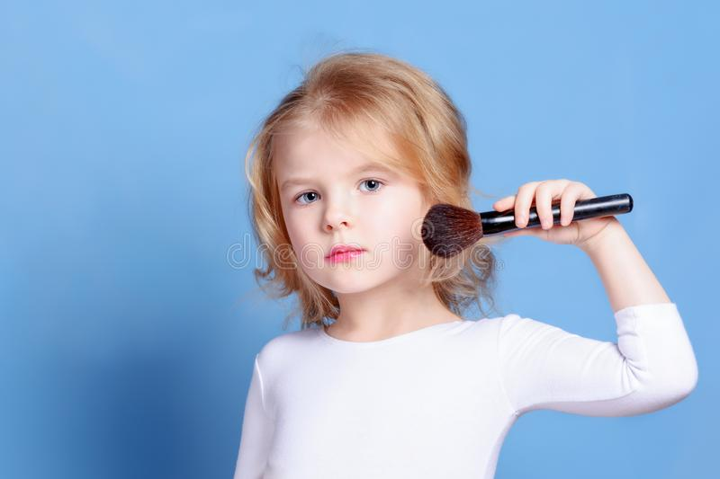 The little girl is powdered with a makeup brush. Beautiful baby with blond hair. Bright advertising photography. stock photography