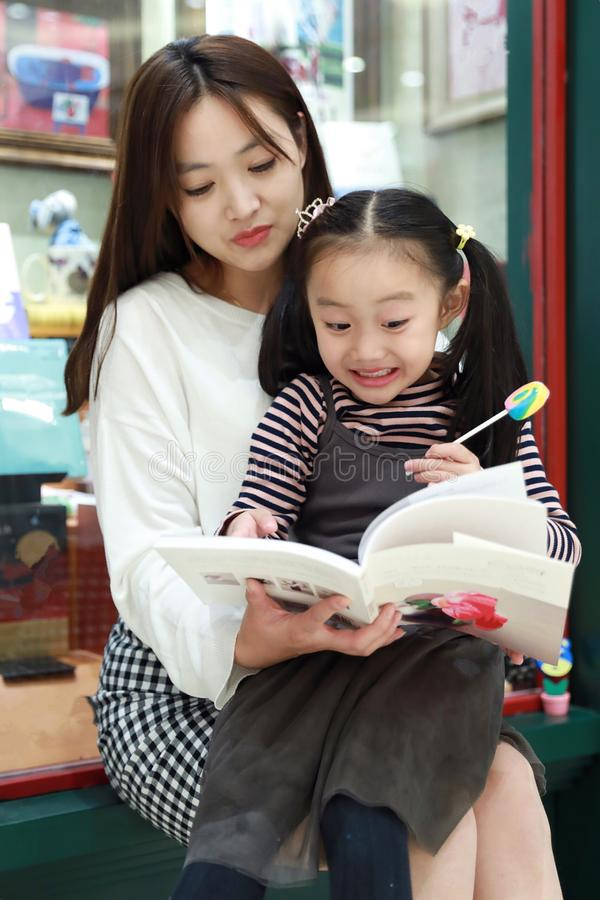 Little girl practice reading in the Brilliantly illuminated Market royalty free stock photos