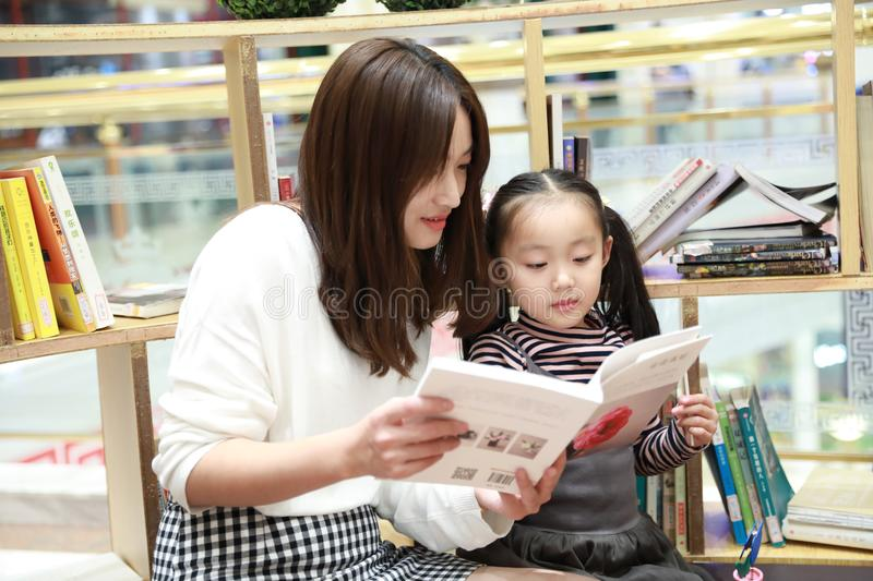 Little girl practice reading in the Brilliantly illuminated Market royalty free stock photography