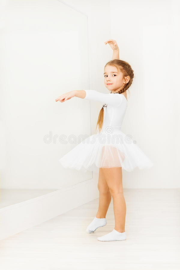 Little girl practicing posture during ballet class. Adorable little girl in white dancewear, practicing posture during ballet class in light hall with copy-space stock image