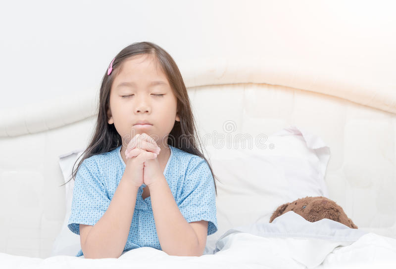 Little girl praying on bed, spirituality and religion. royalty free stock photo