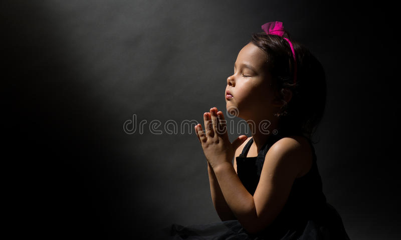 Little girl praying, isolated black background royalty free stock photos