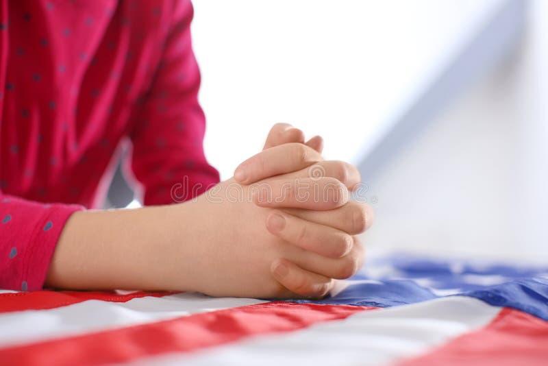 Little girl praying over American flag,. Closeup royalty free stock image