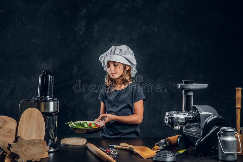 Little girl is prepairing vegetables for cooking stock image