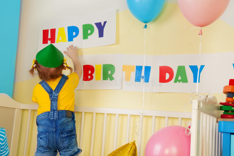 Little girl prepare for birthday party. Hanging a birthday sign royalty free stock image