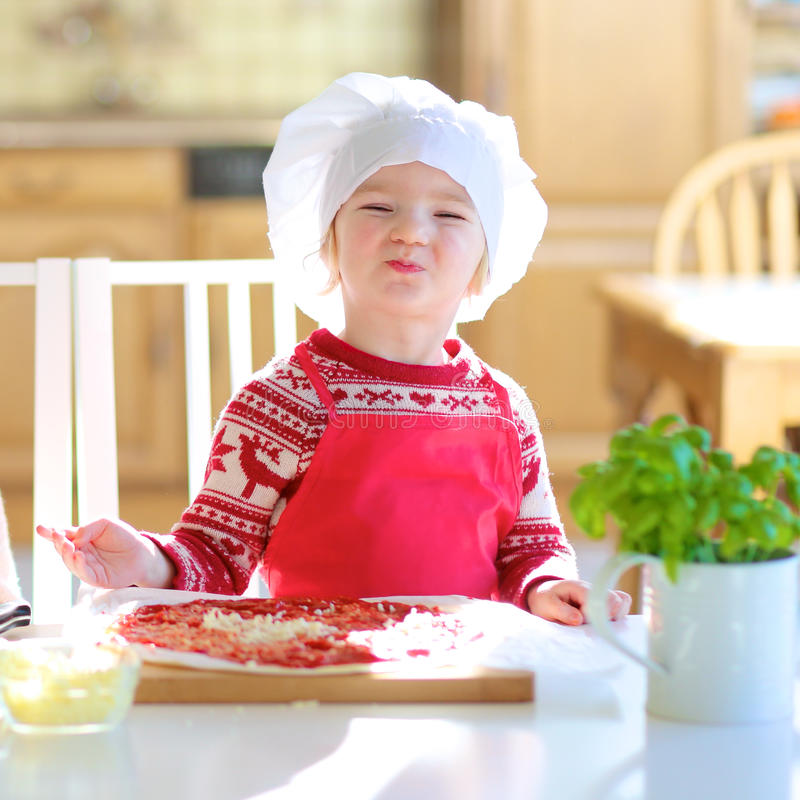 Little girl preparing tasty pizza royalty free stock images