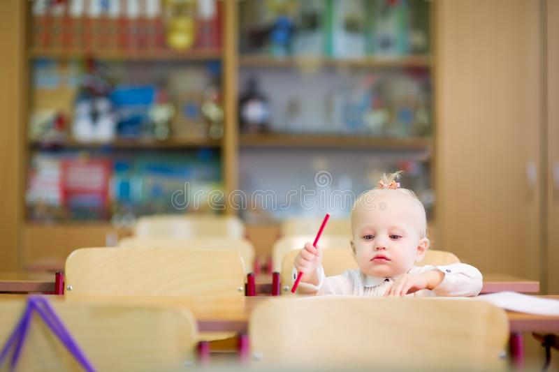 A little girl of preschool age sits at her desk in the classroom and draws with a pencil in the album. A little girl of preschool age sits at her desk and draws stock image