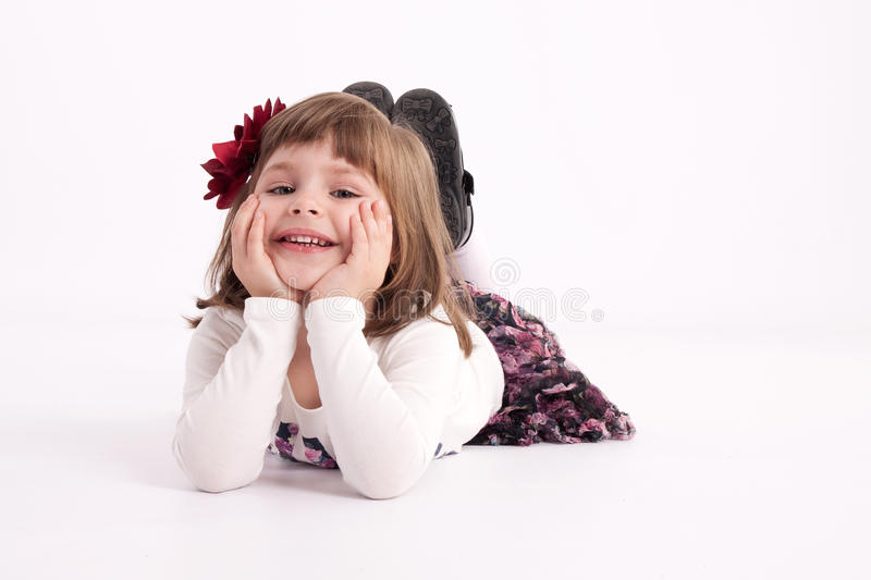 Little girl preschooler model. In a flowered skirt with flower in hair lying comfortably on the floor and smiling royalty free stock photos