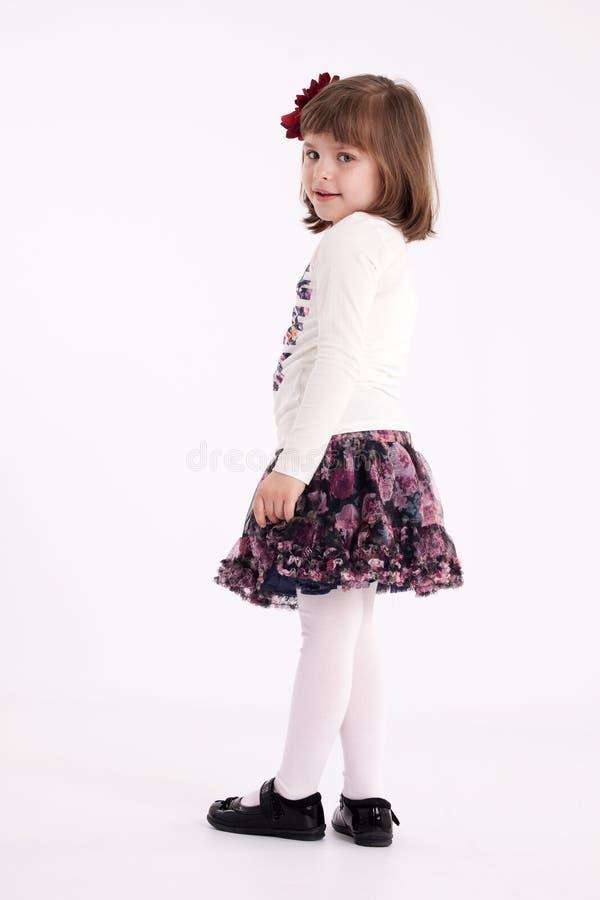 Little girl preschooler model. In a flowered skirt with flower in hair posing standing in studio stock photo