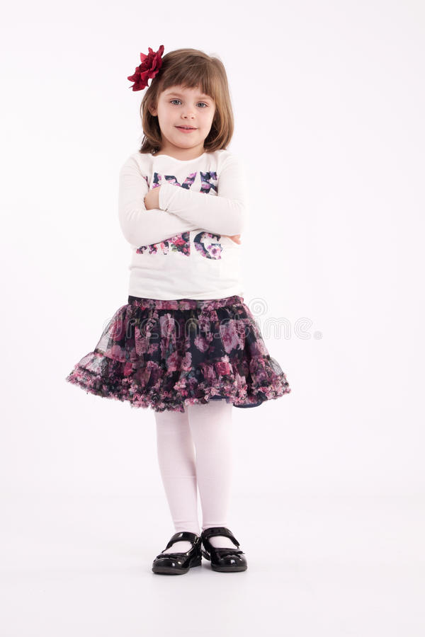 Little girl preschooler model. In a flowered skirt with flower in hair posing standing in studio royalty free stock images