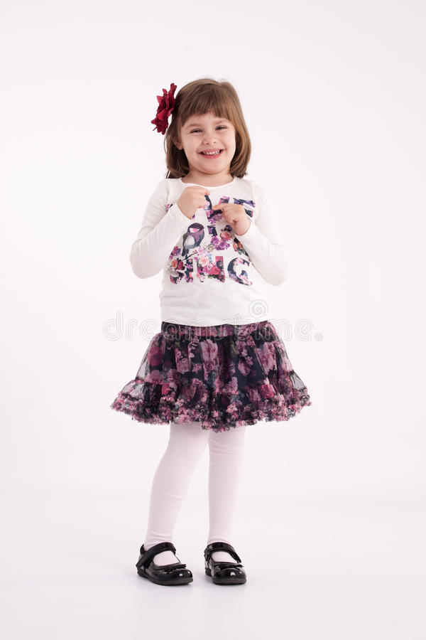Little girl preschooler model. In a flowered skirt with flower in her hair standing makes a mockery royalty free stock photos