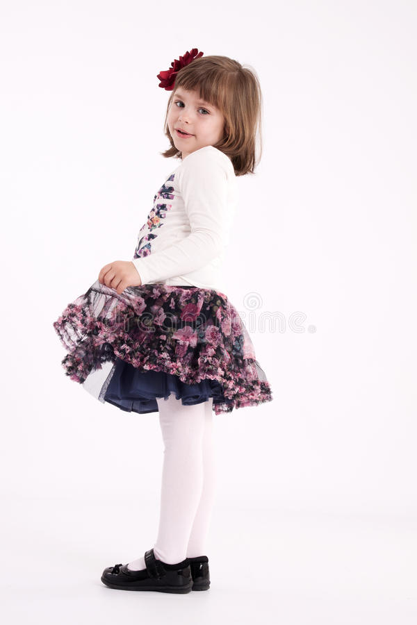 Little girl preschooler model. In a flowered skirt with flower in her hair standing shyly dancing royalty free stock photos