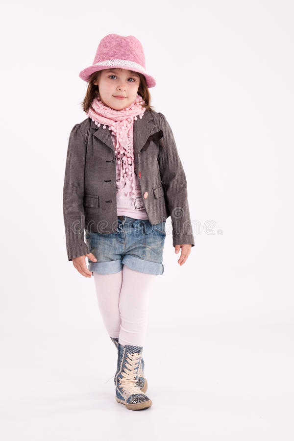 Little girl preschooler model. In pink hat, coat, shorts and sneakers high with a scarf on her neck posing in studio stock photo