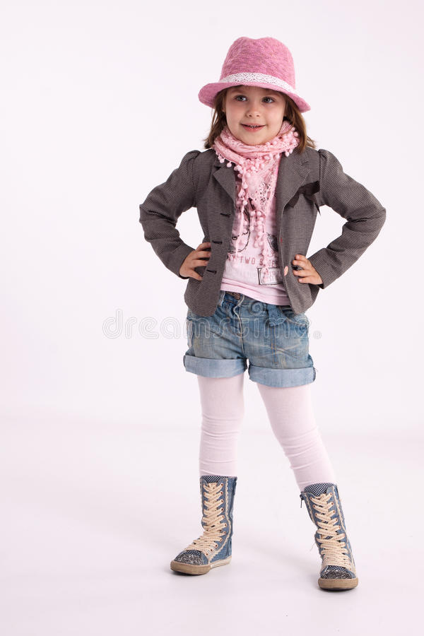 Little girl preschooler model. In pink hat, coat, shorts and sneakers high with a scarf on her neck posing in studio royalty free stock images