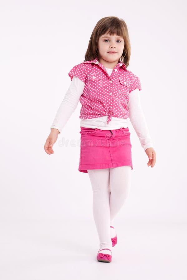 Little girl preschooler model. In pink skirt, sandals and dotted shirt posing in studio stock photos