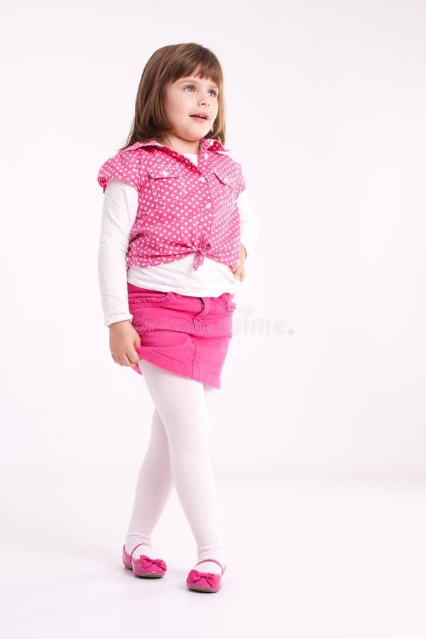 Little girl preschooler model. In pink skirt, sandals and dotted shirt posing in studio stock photography