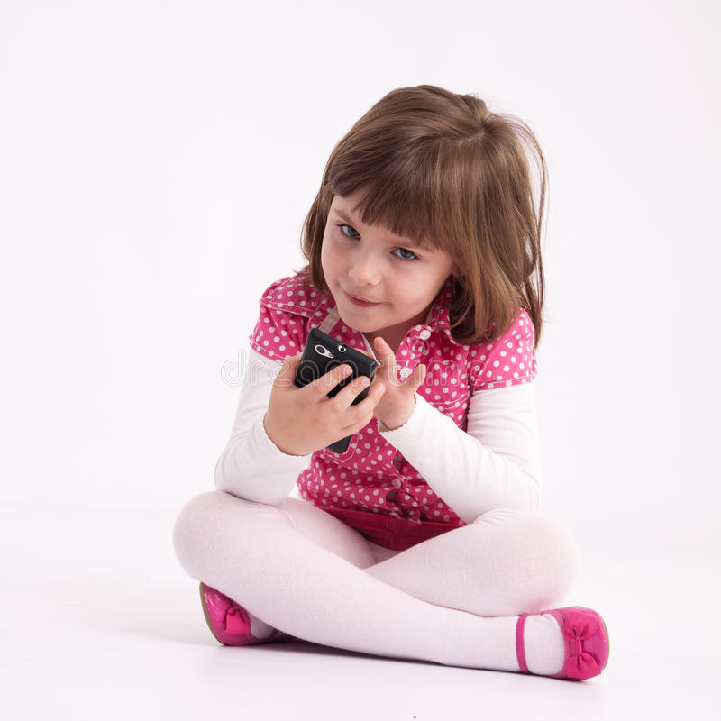 Little girl preschooler model. In pink skirt, sandals and dotted shirt and sitting on the floor with mobile phone stock photos
