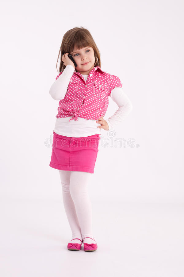 Little girl preschooler model. In pink skirt, sandals and dotted shirt and standing with mobile phone royalty free stock photo