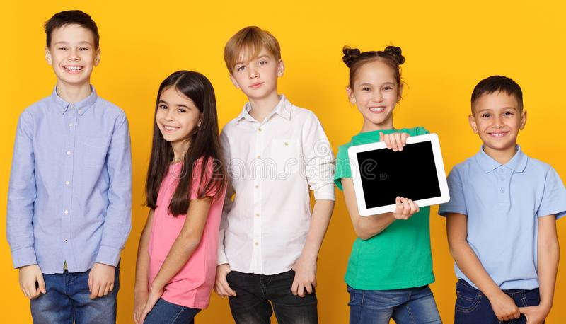 Little girl presenting blank tablet with happy classmates nearby stock photography
