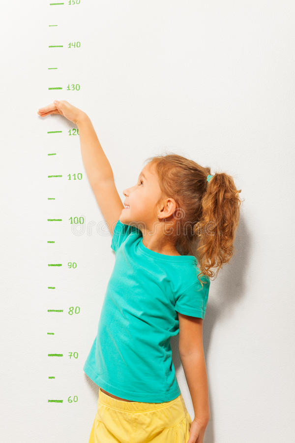 Little girl pretend how high she is on wall scale royalty free stock photos