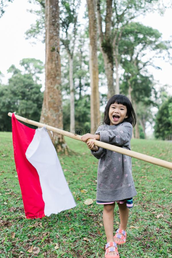 Little girl pride flapping Indonesian flag with happiness. In the garden stock images