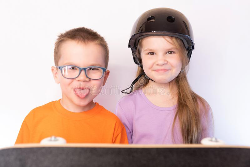 Little girl in protective helmet and a little boy with glasses showing tongue, keep a skateboard, on a light background royalty free stock photography