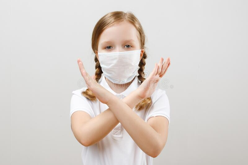 A little girl in a protective medical mask shows a stop gesture with her hands during a coronavirus pandemic. Portrait of a child on a gray background stock photo
