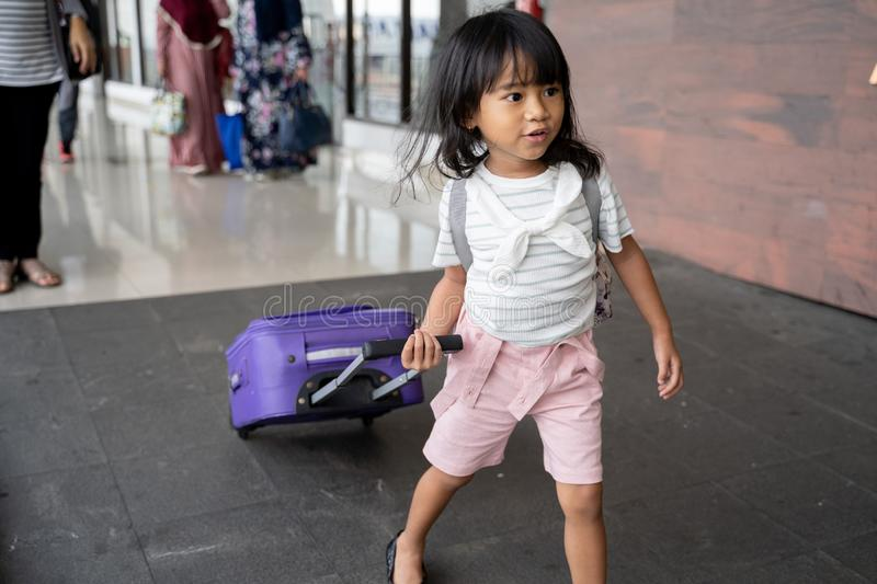 Little girl pulling a suitcase while going on vacation stock photography