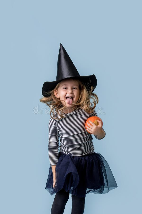 Little girl with a pumpkin in hands and in a witch costume royalty free stock photo