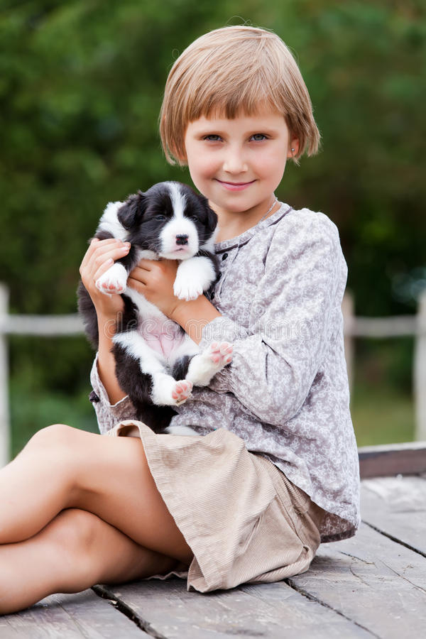 Little girl with the puppy. Border Collie stock image