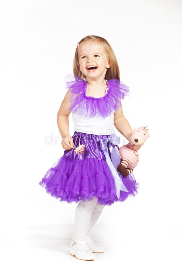 Little girl in a purple skirt. With flower and toy in hand royalty free stock photo