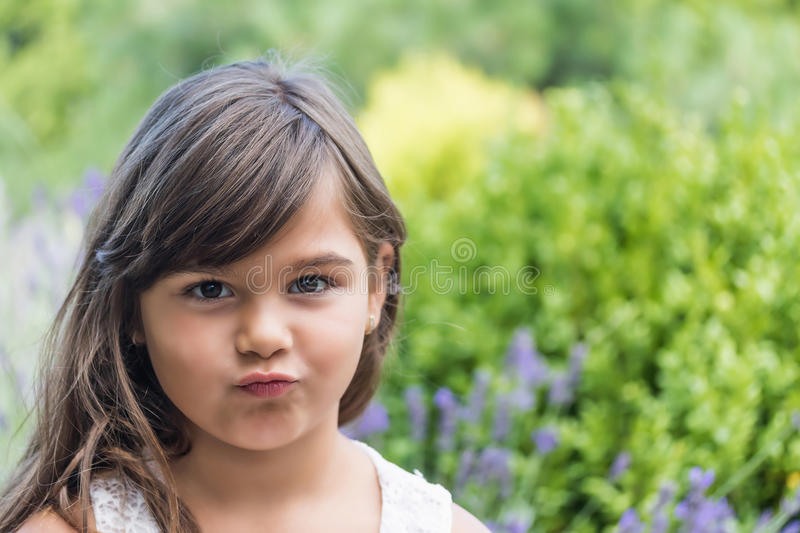 Little girl with pursed lips. Portrait of attractive little girl outdoors. Little girl with pursed lips is looking at the camera stock photo