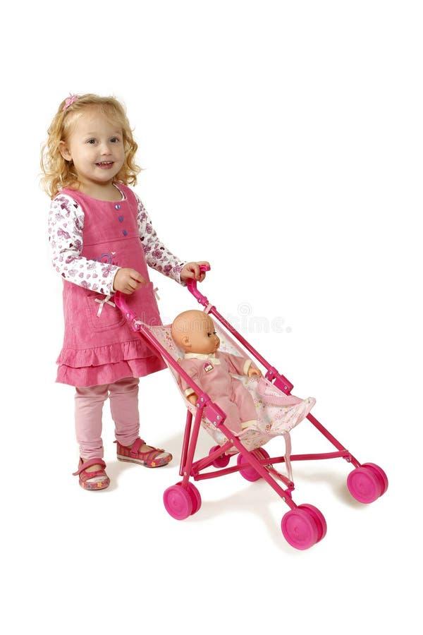 Little girl pushing a pram royalty free stock photography
