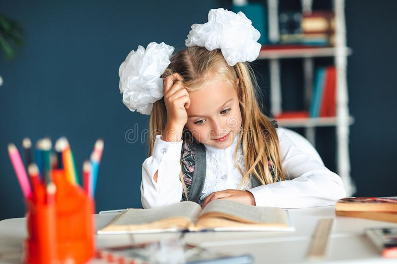 The little girl put her hand behind her head while reading a large book. The difficulties of children`s education. The problem. With understanding the school royalty free stock images