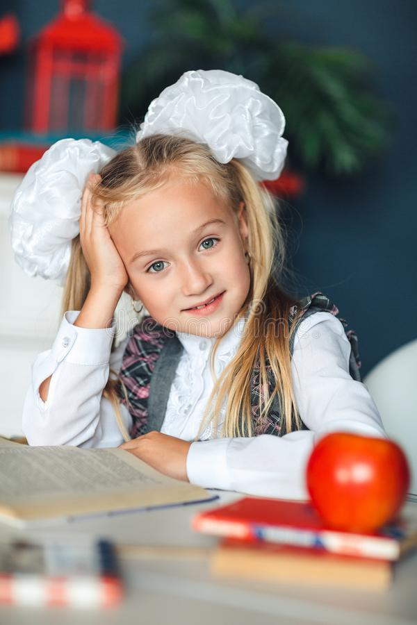 The little girl put her hand behind her head while reading a large book. The difficulties of children`s education. The problem. With understanding the school royalty free stock image
