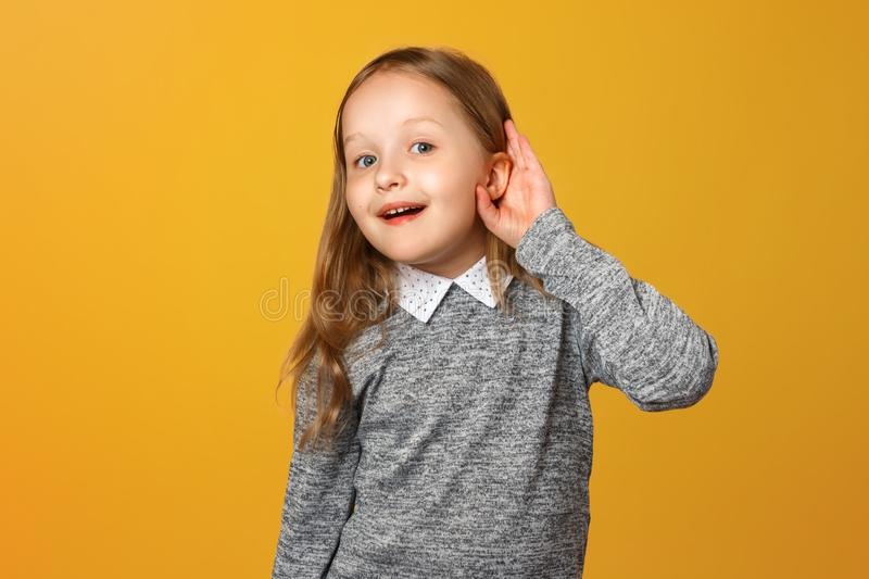 The little girl puts her hand to her ear to hear better. The child is listening to something on a yellow background royalty free stock photography