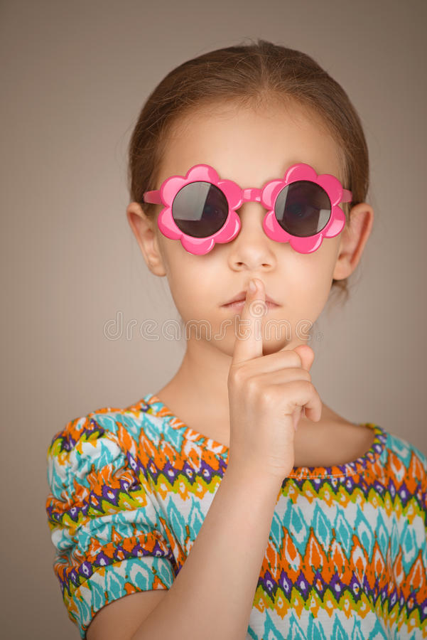 Little girl puts index finger to lips royalty free stock photos