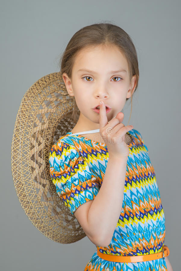 Little girl puts index finger to lips royalty free stock images