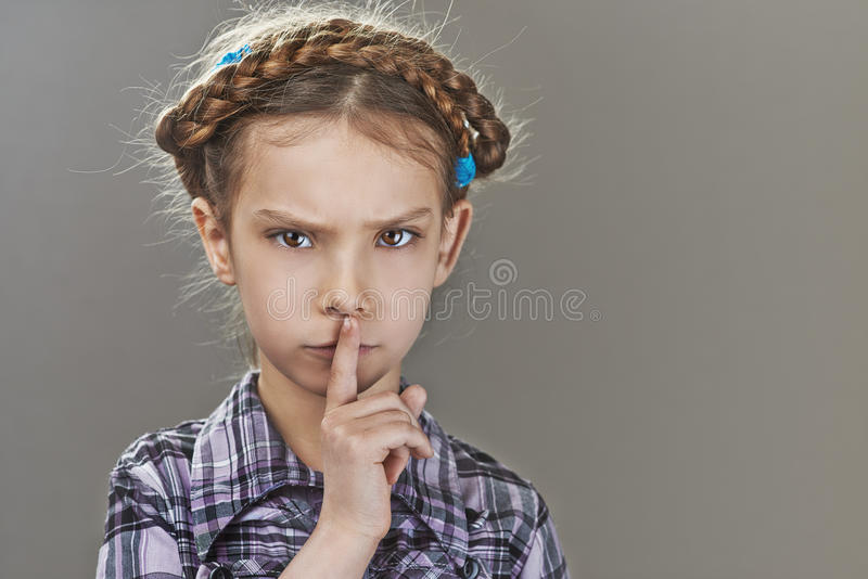 Little girl puts index finger to lips stock images