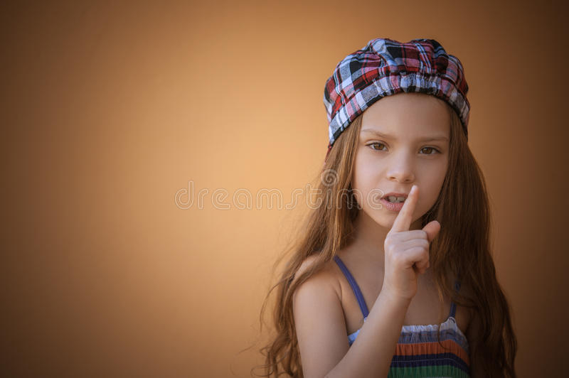 Little girl puts index finger to lips royalty free stock image