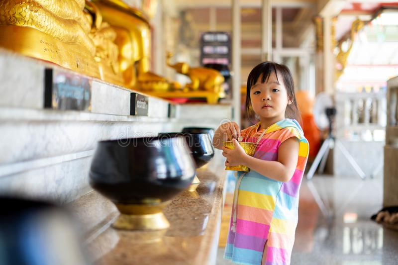Little girl putting coins in one of monk alms bowl for merit in buddhism with lots of monk alms bowls beside in a temple stock image